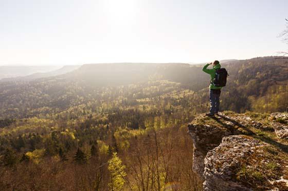 "Albstatt-Onstmettingen, Baden-Württemberg, Germany: A male hiker on the ""Hangender Stein"" cliff along the ""Traufgang Zollernburg-Panorama"" trail."
